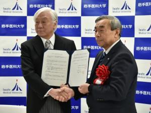 協定書を手に握手を交わす     小川理事長と高橋矢巾町長